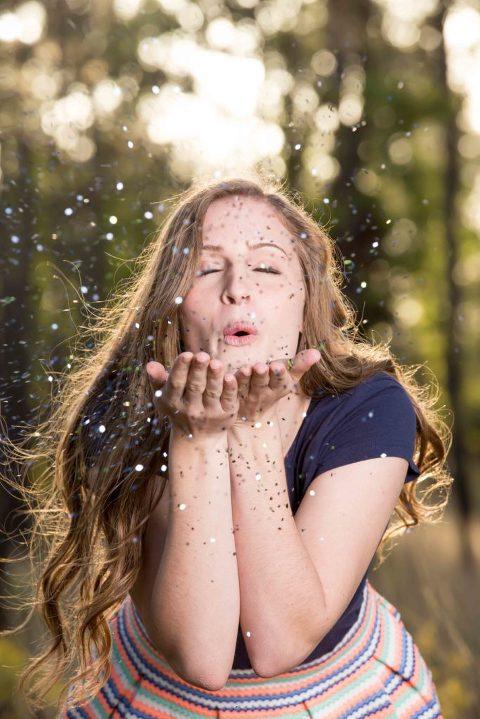 senior girl blowing glitter in ocala